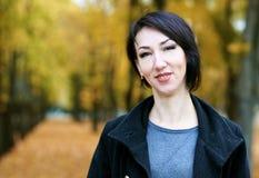 Dziewczyna portret, kolor żółty opuszcza na tle, jesieni miasta park, sezon jesienny, czerń żakiet Zdjęcia Royalty Free