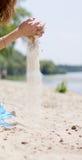 Dziewczyna posypuje piasek z swój ręk Zdjęcia Stock