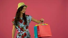 Dziewczyna pozuje na kamerze z stubarwnymi torbami na zakupy Różowy tło zbiory