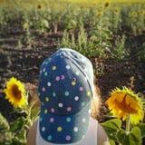 Dziewczyna pozuje przy słonecznikowym polem zdjęcie stock