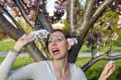 Dziewczyna pozuje z dużymi partyjnymi okularami przeciwsłonecznymi outdoors Obrazy Stock