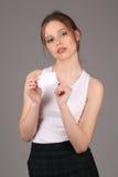 Dziewczyna pozuje z małym sztandarem w ona ręki z bliska Szary tło Obraz Stock