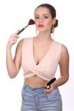 Dziewczyna pozuje z makeup muśnięciem z bliska Biały tło Zdjęcie Royalty Free