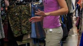 Dziewczyna Próbuje koszulkę przy stojakami z dalej Odziewa w sklepie zbiory wideo