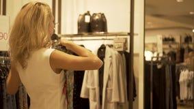 Dziewczyna próbuje na sukni przy lustrem w sklepie odzieżowym zbiory wideo