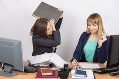Dziewczyna próbuje uderzać jego kolegi w biurze z skoroszytową złością Fotografia Stock