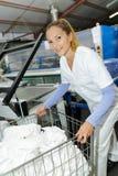 Dziewczyna pracownik trzyma pralnianą furę Fotografia Stock
