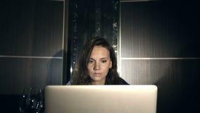 Dziewczyna pracuje na komputerze w wieczór w wnętrzu z wodnym tłem zbiory wideo
