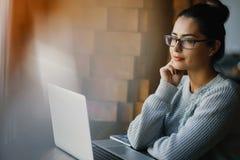 Dziewczyna pracuje na laptopie przy restauracją fotografia stock