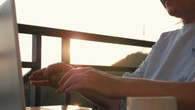 Dziewczyna pracuje z laptopem i filiżanką kawy przy stołem przy zmierzchem w słońcu zbiory wideo