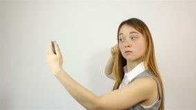 Dziewczyna prostuje jej spojrzenia przy telefonem i włosy zbiory