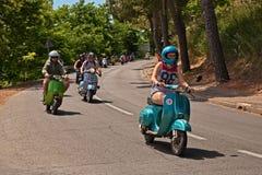 Dziewczyna prowadzi grupy rowerzyści jedzie rocznik włoską hulajnogę Ve fotografia stock