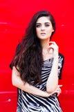 Dziewczyna przeciw czerwonej ścianie Obrazy Royalty Free