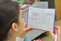 Dziewczyna przy lekci spojrzeniami przy notatnikiem na regułach Rosyjski język Zdjęcia Stock