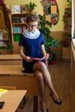 Dziewczyna przy szkolnymi biurkami Zdjęcia Stock