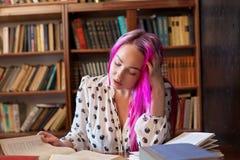 Dziewczyna przygotowywa dla egzaminu czyta mnóstwo książki w bibliotece zdjęcia royalty free