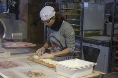 Dziewczyna przygotowywa pizzę wśrodku środkowego rynku Fotografia Royalty Free