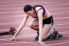Dziewczyna przygotowywająca zaczynać biegać na bieg śladzie Zdjęcie Stock