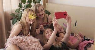 Dziewczyna przyjaciele bierze selfie podczas gdy pozujący z sfałszowanymi wsparciami na łóżku zbiory