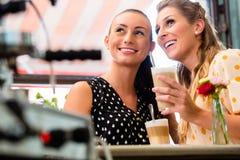 Dziewczyna przyjaciele pije latte macchiato w kawowym barze obraz stock