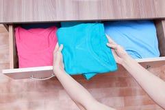 Dziewczyna ręki biorą za odziewa od dresser Odgórny widok, zakończenie obraz royalty free