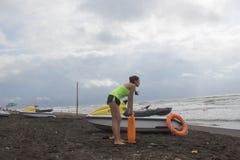 Dziewczyna ratownik utrzymuje boja przy plażą na obowiązku Wodna hulajnoga, ratownika sprzętu ratowniczego preserver pomarańczowy Obrazy Stock