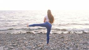 Dziewczyna robi ćwiczenia lunge, nogi dźwignięcie bodyflex podczas oddychania ćwiczy na dennym tle zbiory