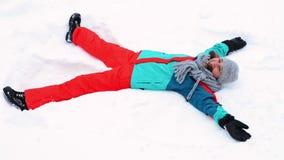 Dziewczyna robi śnieżnemu aniołowi zbiory