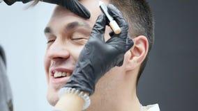 Dziewczyna robi do mężczyzna fachowy makijażu artysty makeup brew zbiory