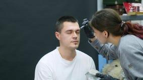 Dziewczyna robi do mężczyzna fachowy makijażu artysty makeup brew zdjęcie wideo