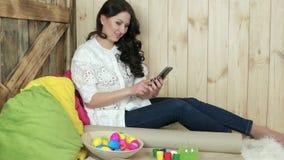 Dziewczyna robi fotografii łozinowy półkowy pełny Easter jajka, uśmiechnięta młoda kobieta photoshooting zbiory wideo