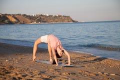 Dziewczyna robi gimnastykom w ranku na Plażowym oceanie zdjęcia royalty free