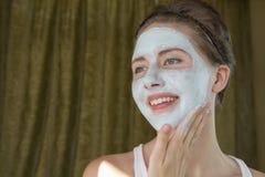Dziewczyna robi kosmetyk masce na jej twarzy obraz royalty free