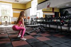 Dziewczyna robi kucnięciom w gym obrazy stock