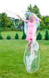 Dziewczyna robi mydlanym bąblom w domu ogródzie Obraz Stock