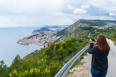 Dziewczyna Robi obrazkom od Dubrovnik na wzgórzu z mądrze telefonem w małej drodze Stary miasteczko w Chorwacja fotografia stock