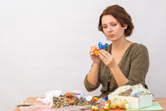 Dziewczyna robi ogonowi zabawkarski cockerel od dekoracyjnego faborku wokoło stołu z uszyciem Obrazy Royalty Free