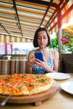 Dziewczyna robi pizz fotografiom na telefonie Zdjęcie Royalty Free
