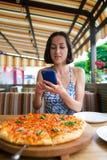 Dziewczyna robi pizz fotografiom na telefonie Fotografia Royalty Free