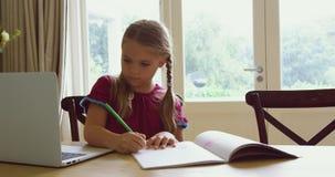 Dziewczyna robi pracie domowej przy łomotać stół w wygodnym domu 4k zdjęcie wideo
