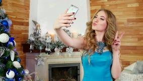 Dziewczyna robi selfie, Bożenarodzeniowa fotografia telefon komórkowy, świąteczny przyjęcie przy choinki piękną dziewczyną używa  zbiory wideo