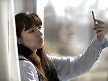 Dziewczyna robi selfie podczas gdy siedzący okno zdjęcie stock