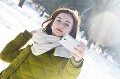 Dziewczyna robi selfie w zima parku Fotografia Royalty Free