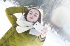 Dziewczyna robi selfie w zima parku Zdjęcia Royalty Free