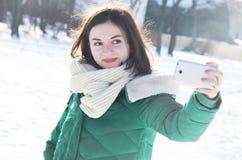 Dziewczyna robi selfie w zima parku Obraz Stock