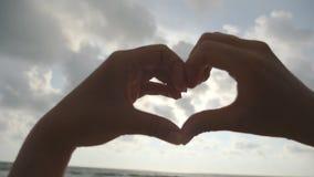 Dziewczyna robi sercu z jej rękami nad dennym tłem z pięknym złotym zmierzchem Sylwetka żeńska ręka w sercu zdjęcie wideo