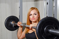 Dziewczyna robi ćwiczeniom z barbell w gym Zdjęcia Royalty Free