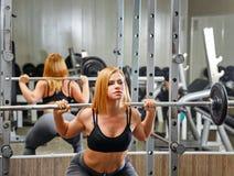 Dziewczyna robi ćwiczeniom z barbell w gym Zdjęcie Royalty Free