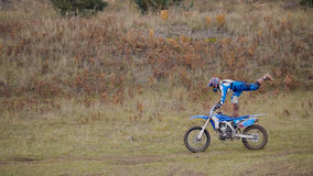 Dziewczyna roweru przedstawienia akrobatyczni przy MX moto krzyżem ściga się - jeździec na brudu motocyklu Zdjęcie Stock