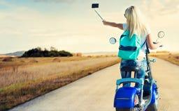 Dziewczyna rowerzysta siedzi na motocyklu i fotografował Relaksuje po wycieczki fotografia royalty free